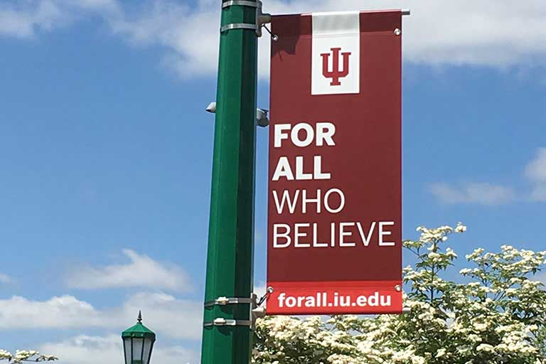 IU For all who believe banner on IU campus