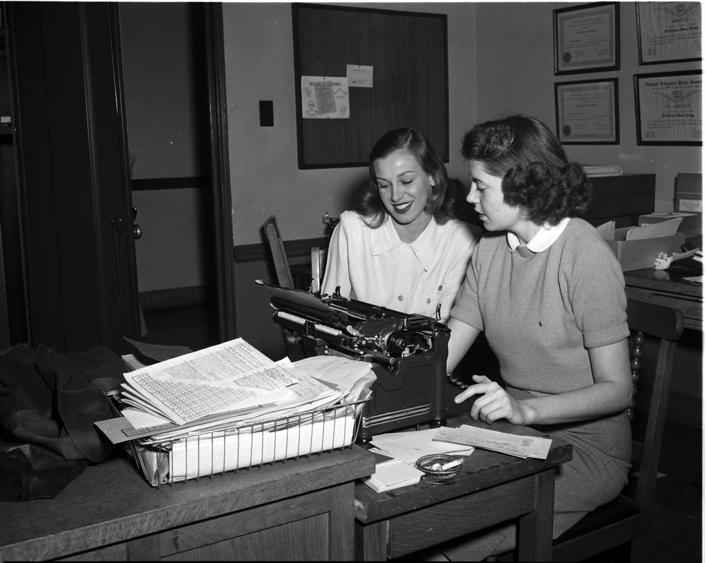 Black and white photo of IU office staff stting at a typewriter